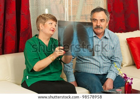 Doctor woman showing x-ray to senior man in his house
