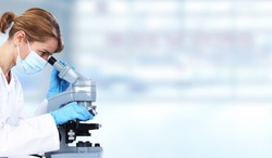 Doctor woman with microscope in laboratory. Scientific research.