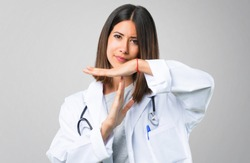 Doctor woman with stethoscope making stop gesture with her hand to stop an act on grey background