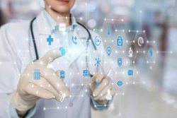 Doctor working on a virtual screen behind the structure of medical icons on a blurred background.