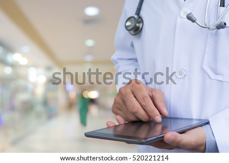 Doctor working on digital tablet computer in hospital. Electronic medical records system, electronic health records system, EMRs, EHRs concept