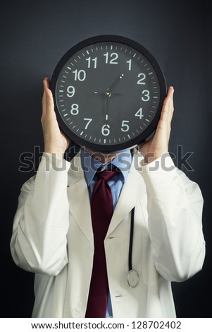 Doctor working overtime, holding a black clock in front of his head. Overtime work, not enough time, time pressure, deadline concept, time management, clock face.