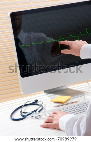Doctor working with computer and electrocardiogram