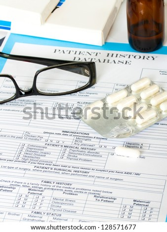 Doctor workplace. Pills, tablets, glasses on patient history database