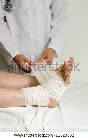 Doctor wrapping a patient's ankle with a bandage. Isolated.