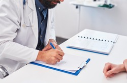 Doctor writing a prescription for his patient