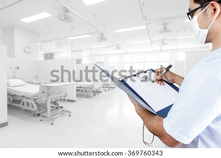 Doctor writing clipboard for diagnosis in aided the recovery room with modern equipment and comfortable equipped in hospital