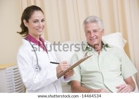 Doctor writing on clipboard while giving checkup to man in exam room smiling