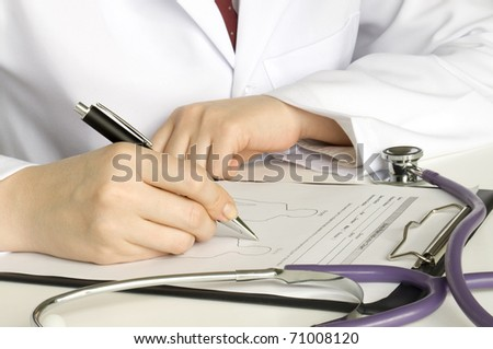 doctor writing on the clipboard and stethoscope on the table - stock photo