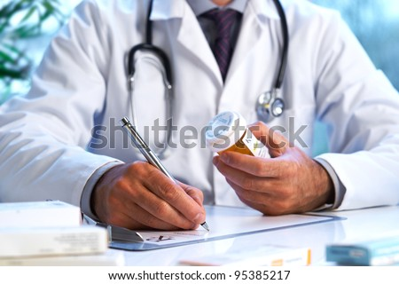 Doctor writing out RX prescription selective focus
