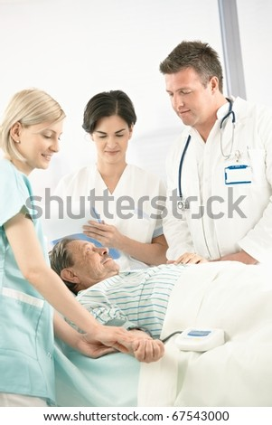 Doctors and nurse examining old patient in hospital, nurse measuring blood pressure.?