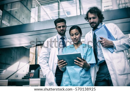 Doctors and nurse looking at digital tablet in hospital