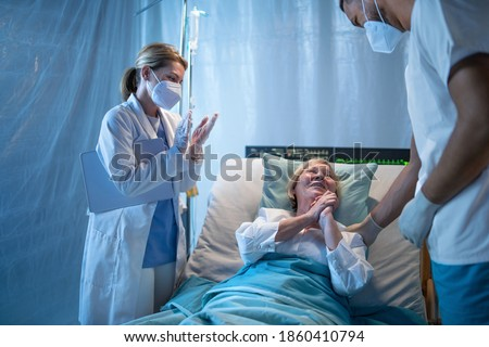 Doctors and recovered covid-19 patient in bed in hospital, coronavirus and recovery concept. Foto stock ©