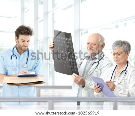 Doctors discussing diagnosis in hospital lobby, team lead by experienced professor. - stock photo