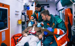 Doctors emergency or paramedics are working with a senior man patient while he lies on a stretcher in an ambulance.