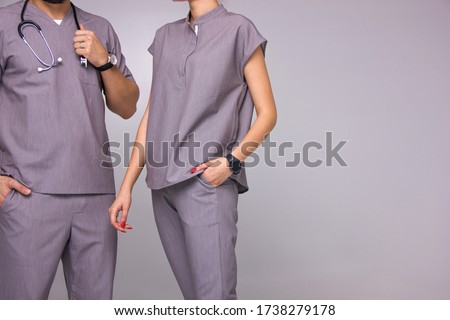 doctors group. close-up male and female nurses in medical costumes with stethoscope on neck are standing fashion like team  on the gray wall background, medical concept, free space on right side Stockfoto ©