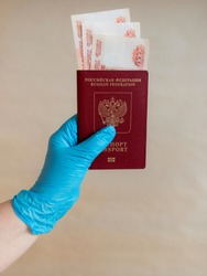 Doctors hand in a blue medical glove holding Russian passport with 5000 rubles cash money, banknotes inside the passport on a white background, close up on the center