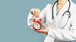 Doctors hands holding red alarm clock over blue background. Time is crucial life saver. Medical banner. Copy space. Book appointment or checkup time reminder.
