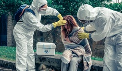 Doctors in bacteriological protection suits caring for a woman infected by a virus outdoors