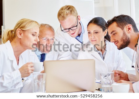 Doctors in meeting looking at computer together