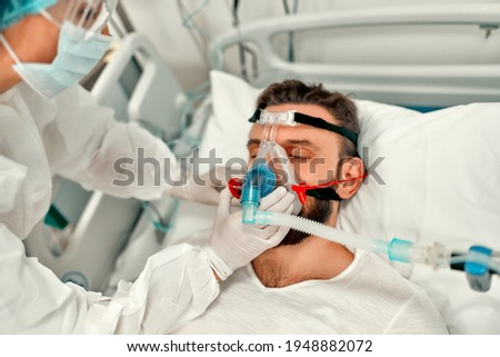 Doctors in protective suits put on a ventilation mask on a sick man with coronavirus disease covid-19, who is in an intensive care unit in a modern hospital. Photo stock ©