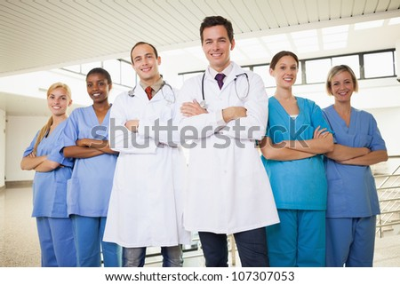 Doctors with nurses with arms crossed in hospital corridor