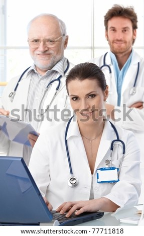 Doctors working at desk, female doctor in front, looking at camera, smiling.?