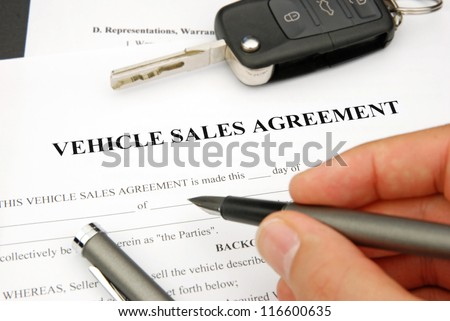 Document and Form of a Vehicle Sales Agreement with Hand signing pen and car key
