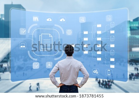 Document Management System (DMS) used to archive, search and manage corporate files and information in enterprise along business processes. Concept with manager looking at screen Stockfoto ©