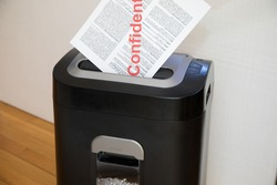 Document marked confidential going into shredder