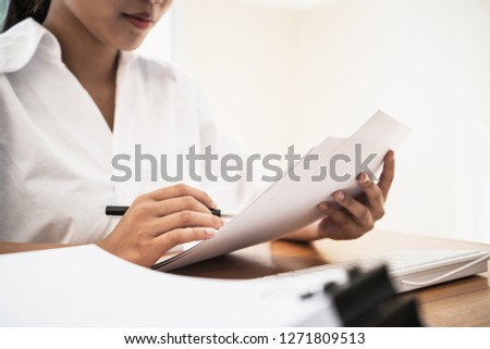 Document Report business busy Concept: Asian Young Businesswoman or University Student reading documents reports papers before sign on stacks of paper in home office with calculator laptop computer