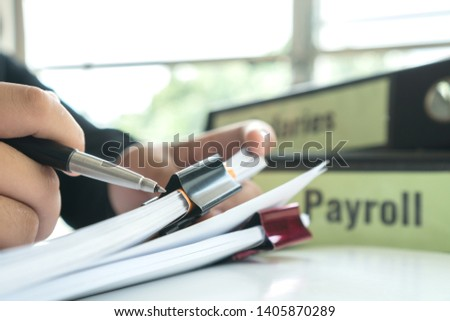 Document report or business management concept: Businessman manager hands holding pen for reading, signing paperwork near payroll salary binder, Work from Home and Learn studying prevent Covid-19