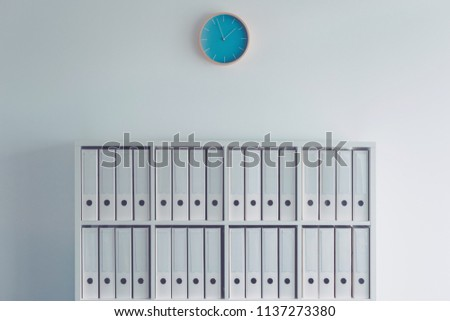 Document ring binders in business office with clock on the wall as conceptual image for fiscal year bookkeeping and tax accounting with copy space included