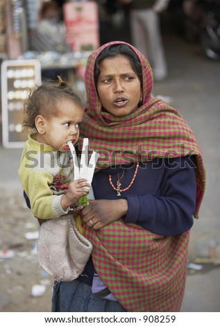 Documentary: Life in India. Poor mother with baby at the streets of New Delhi