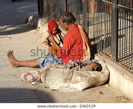 Documentary: Life in India. Widower witht two small babies begging for food at the streets of Jaipur, India.