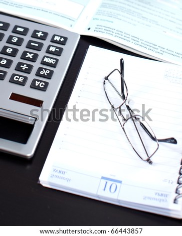 Documents, a  calculator, eyeglasses on the black table