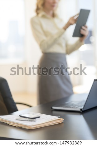 Documents and laptop on desk with businesswoman using digital tablet in background at office