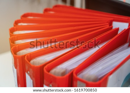Documents Binder Paper, Red Files folder on office desk, Annual Report document for Business papers financial market in offices, lawyer research achieves. Concept work hard or a lot information
