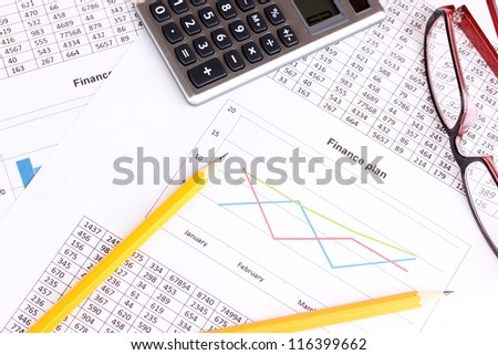 Documents, calculator and glasses close-up