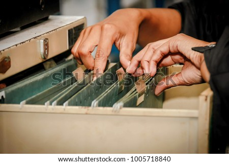 Documents in the office : Find the file in the drawer : Woman working hand searching for file in drawer, filing cabinet.