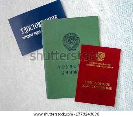 Documents of a Russian pensioner. Background with an old-style work book, a pension certificate and a certificate of a labor veteran.