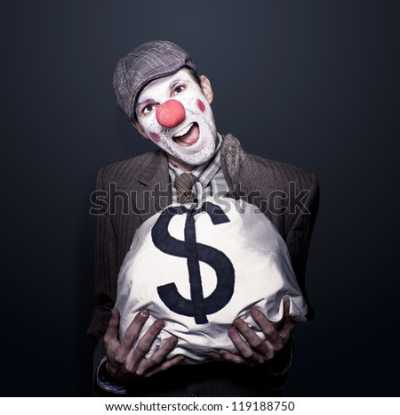 Dodgy Bank Robber Clown Holding Dollar Sign Money Bag While Laughing Out Loud In A Depiction Of Funny Money