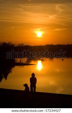 Dog and dog owner watching the sun set - stock photo