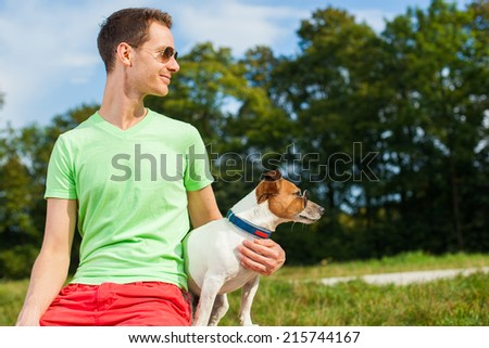 dog and owner observing together , sitting very close together having a good time outdoors