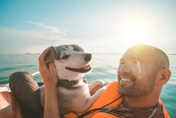 Dog and owner on yacht board on the sunset. Friendship concept. Orange yacht and life-jacket. Funny smiling dog.