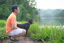 Dog facing foggy lake together with adult man inside a forest. Outdoor recreation concept.