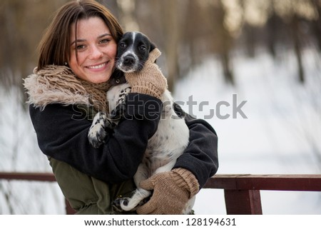 dog in the hands of the owner smiling girl