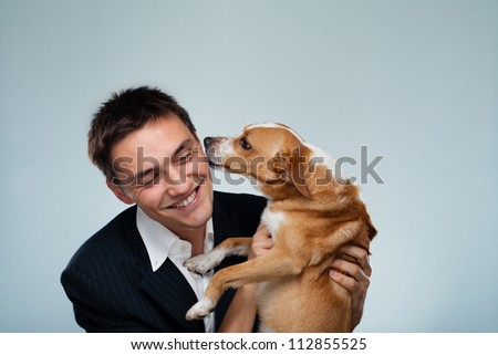 Dog kissing his owner - Young business man have fun with his dog