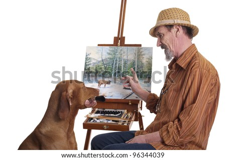 dog listening to man while holding in mouth a paint brush