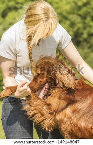 Dog owner cuddling with his irish setter